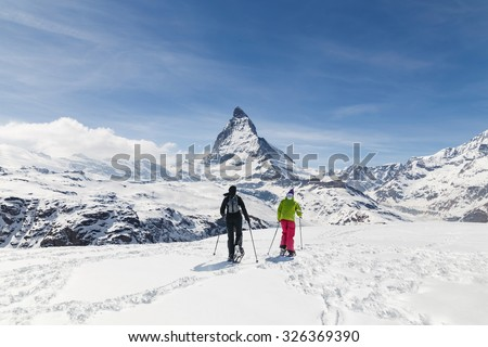 Men walking on ski in the background of Matterhorn, Zermatt, Switzerland. - stock photo