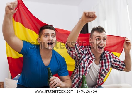 Men watching football match on TV and cheering of spanish team  - stock photo