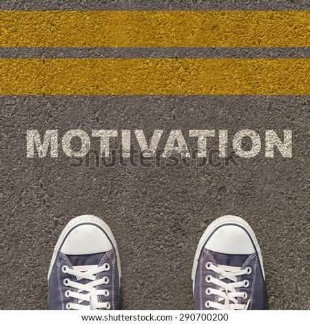 Men wear sneakers, standing on asphalt road area with yellow stripes and lettering motivation. - stock photo