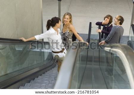 Men whistling at women on the escalator. - stock photo