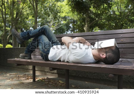 Men who take a nap on a park bench - stock photo