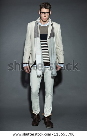 Men winter fashion. Handsome man with brown hair wearing grey scarf, striped sweater, white striped jacket, white pants and black glasses. Casual look. Studio shot isolated on grey background. - stock photo
