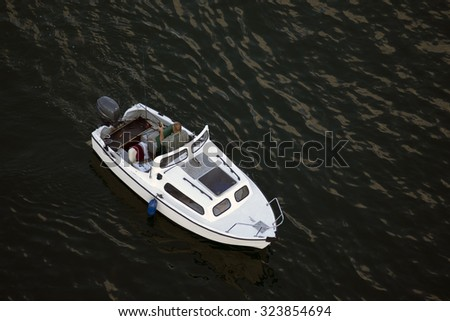 Men with a fish in his hand on a small boat with outboard engine floats through blue sea waves - stock photo
