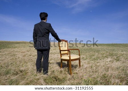 Men with an armchair looking to the horizon - stock photo