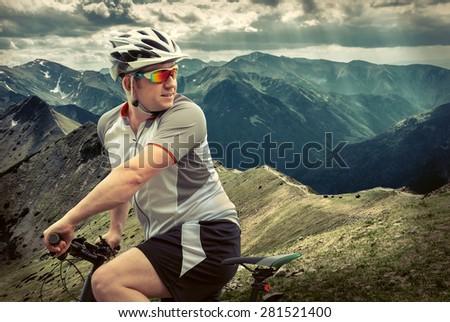 Men with bicycle aroun mountains beautiful view. - stock photo