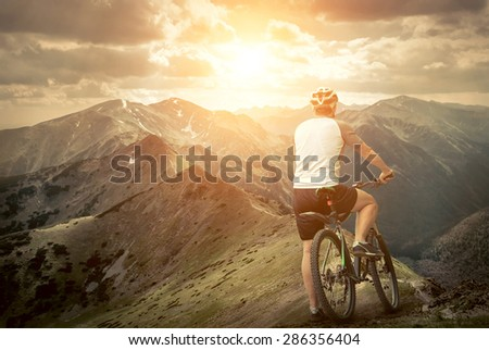 Men with bicycle aroun mountains beautiful view. - stock photo