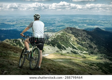 Men with bicycle around mountains beautiful view. - stock photo