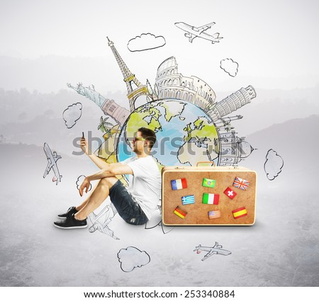 men with cellphone sitting near travel suitcase - stock photo