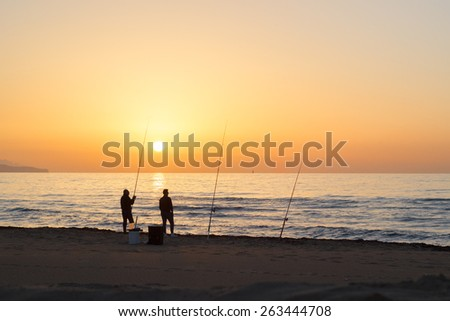 Men with fishing rods at sunset on sea beach  - stock photo