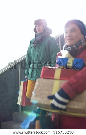 Men with gift boxes and shopping bags standing on steps - stock photo