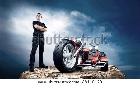 Men with motorbike on the top of mountains. - stock photo