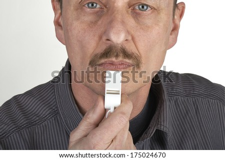 Men with whistle. Referee with whistle on grey background - stock photo