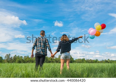 Men, women, Asian green meadow with colored balloons. - stock photo