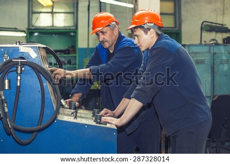 Men work on the old factory for the installation of equipment in protective helmets - stock photo
