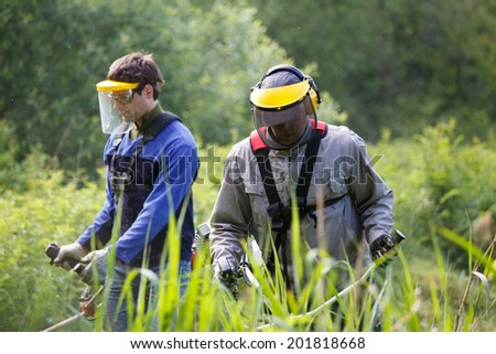 Men working with grass trimmer - stock photo