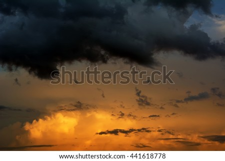 Menacing dark blue clouds cover the sun. The evening sunset - stock photo
