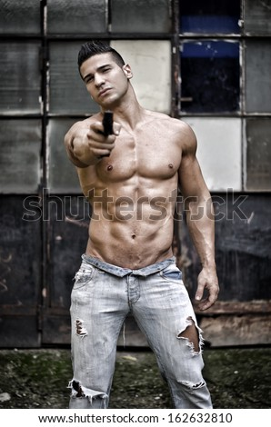 Menacing, muscular young man shirtless pointing handgun to camera outdoors - stock photo
