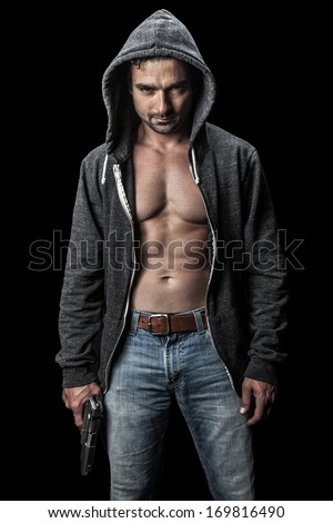 Menacing young man in a hoodie holding a gun. - stock photo