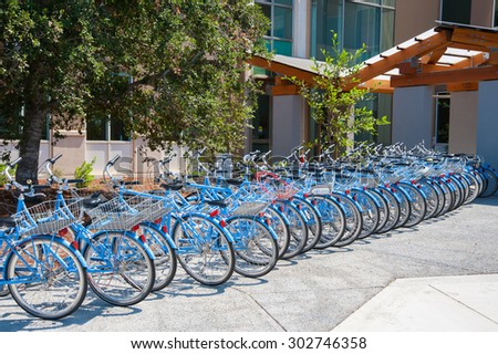 MENLO PARK, CA - AUGUST 1: Bicycles used by FaceBook employees to navigate their campus are parked at Facebook's world headquarters located in Menlo Park, California on August 1, 2015. - stock photo