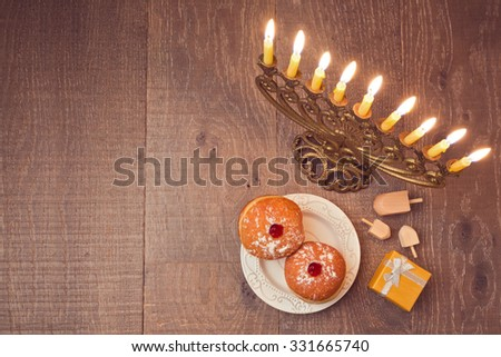 Menorah and sufganiyot on wooden table for Hanukkah celebration. View from above - stock photo