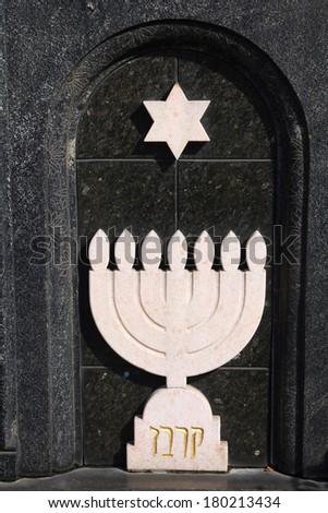 Menorah - Jewish symbol in a grave stone in Milan Monumental Cemetery - stock photo
