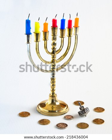 Menorah with candles, silver dreidel and Israelis coins for Hanukkah Celebration. - stock photo