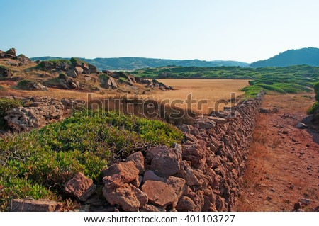 Menorca, Balearic Islands: red sand and wheat field on the path to Cala Pregonda on July 15, 2013. Cala Pregonda is a secluded cove with rocks and red sand: its beach looks like the planet of Mars