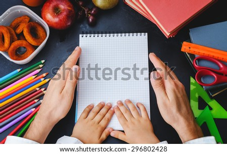 Mens and childrens hands holding a notebook. School concept. the toning. selective focus - stock photo