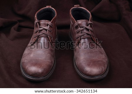 Mens brown shoes  on brown background - stock photo