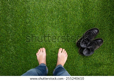 Mens feet resting on green grass