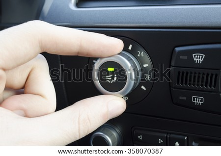 Mens hand setting up the temperature on car climate control system