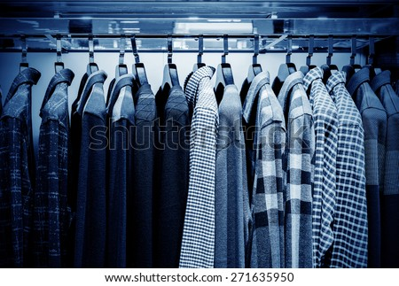Mens plaid shirts on hangers in a retail store - stock photo