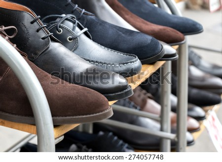 Mens shoes on display on rack outside shoeshop - stock photo