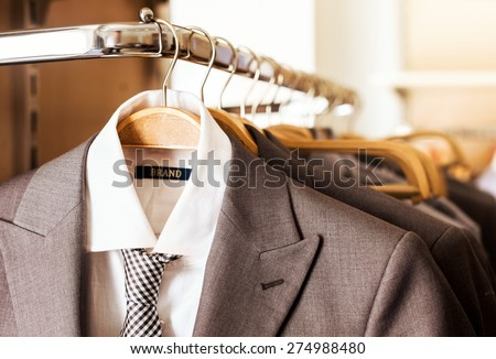 Mens suits on hangers in a clothes store - stock photo