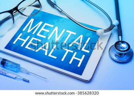 Mental health word on tablet screen with medical equipment on background - stock photo