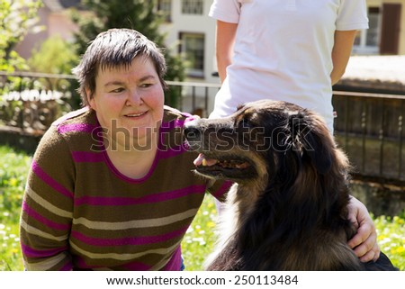 mentally disabled woman is caress a dog - stock photo
