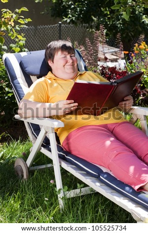 mentally disabled woman reading a book in the garden - stock photo