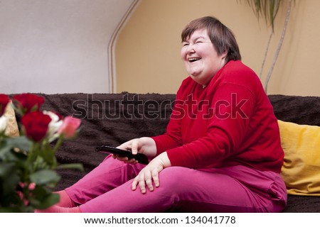 Mentally disabled woman watching television and laughs - stock photo