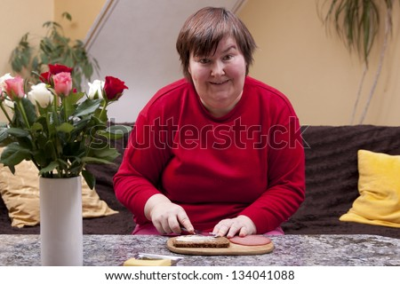 Mentally handicapped woman is making up a sandwich - stock photo