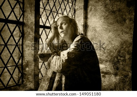 Mentally ill woman looking out of a window in a medieval building,  - stock photo