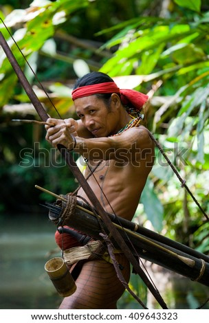 MENTAWAI PEOPLE, WEST SUMATRA, SIBERUT ISLAND, INDONESIA ?? 16 NOVEMBER 2010: Man hunter Mentawai tribe with a bow and arrow in the jungle. 16 November, 2010. West Sumatra, Siberut island, Indonesia.