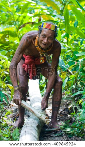 MENTAWAI PEOPLE, WEST SUMATRA, SIBERUT ISLAND, INDONESIA ?? 16 NOVEMBER 2010: Man Mentawai tribe in the jungle makes his clothes from the tree bark.16 November, 2010.Sumatra, Siberut island, Indonesia. - stock photo