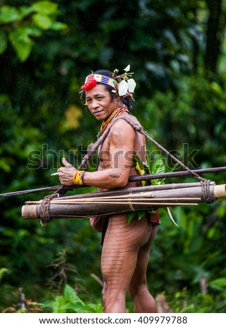 MENTAWAI PEOPLE, WEST SUMATRA, SIBERUT ISLAND, INDONESIA â?? 03 OKTOBER 2011: Man hunter Mentawai tribe with a bow and arrow in the jungle. 03 October, 2011. West Sumatra, Siberut island, Indonesia.
