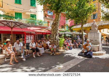 MENTON, FRANCE - AUGUST 15, 2014: People listening to street musician in old town of Menton - popular resort on French Riviera, famous for gardens and Lemon Festival taking place every February. - stock photo