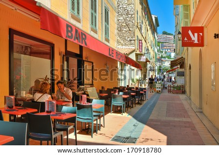 MENTON - JUNE 13: Bars, restaurants and shops on narrow street in old part of town on French Riviera - popular resort with tourists from around the world in Menton, France on June 13, 2013. - stock photo