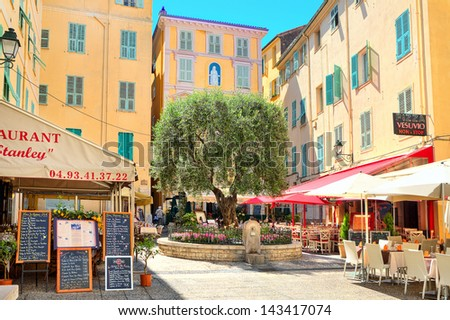 MENTON - JUNE 13: Small square with bars and restaurants surrounded by yellow houses in town on French Riviera - popular resort with tourists from around the world in Menton, France on June 13, 2013. - stock photo
