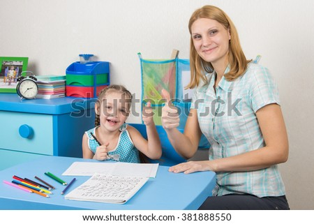 Mentor and five-year girl joyfully show the thumbs up by doing a regular job - stock photo