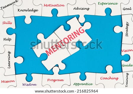Mentoring concept word cloud on group of jigsaw puzzle pieces - stock photo