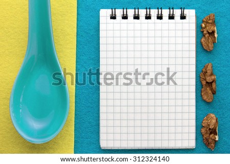 Menu background. Cook book. Recipe notepad with walnuts on a blue and yellow background.  - stock photo
