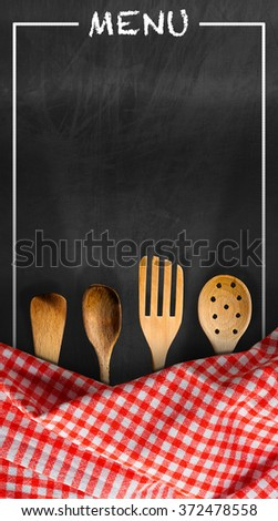 Menu - Blackboard with Kitchen Utensils / Empty blackboard with red and white checkered tablecloth, text Menu and four wooden kitchen utensils. Template for a food menu - stock photo